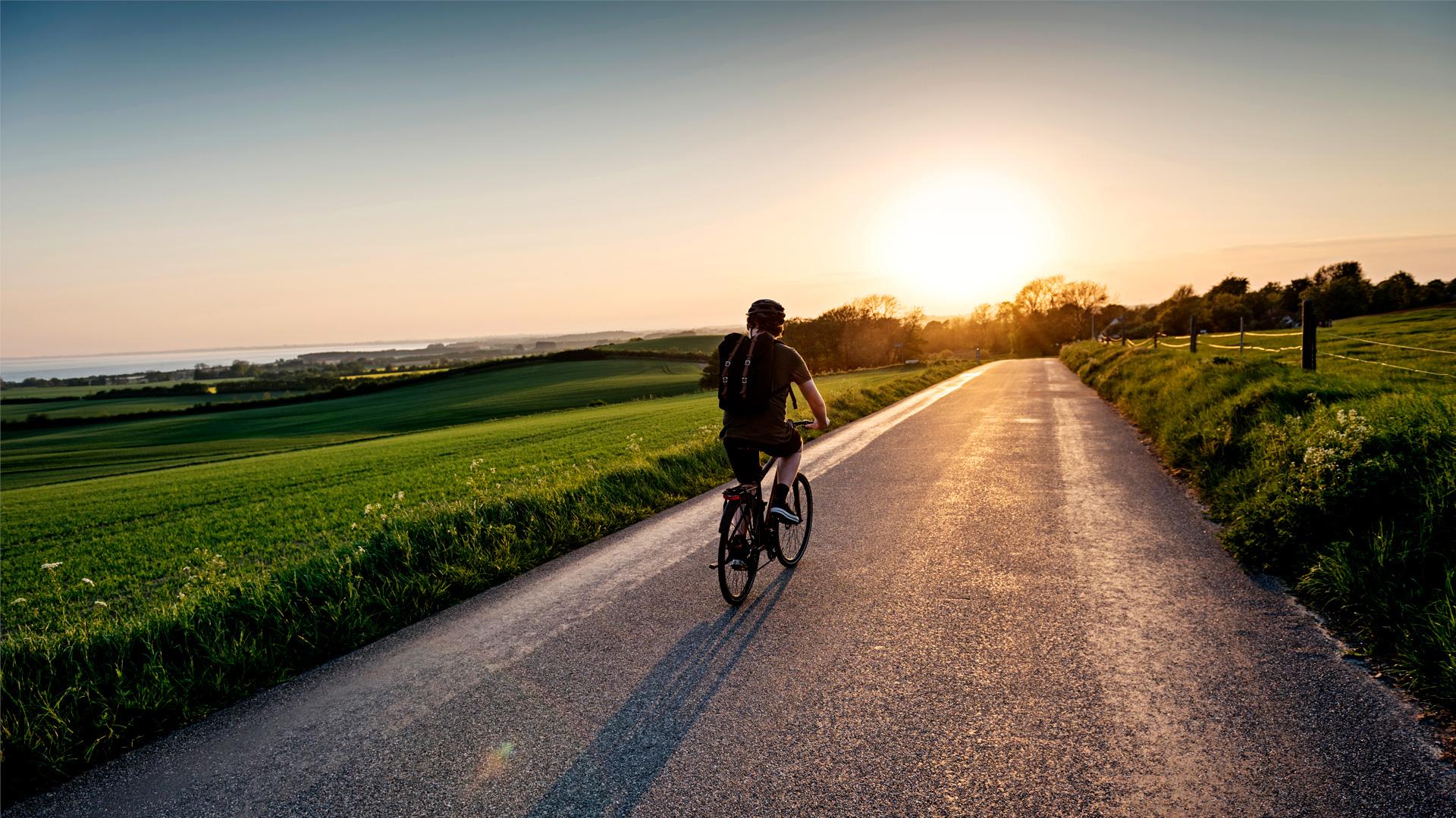Polkupyöräilijä auringonlaskussa hiekkatiellä