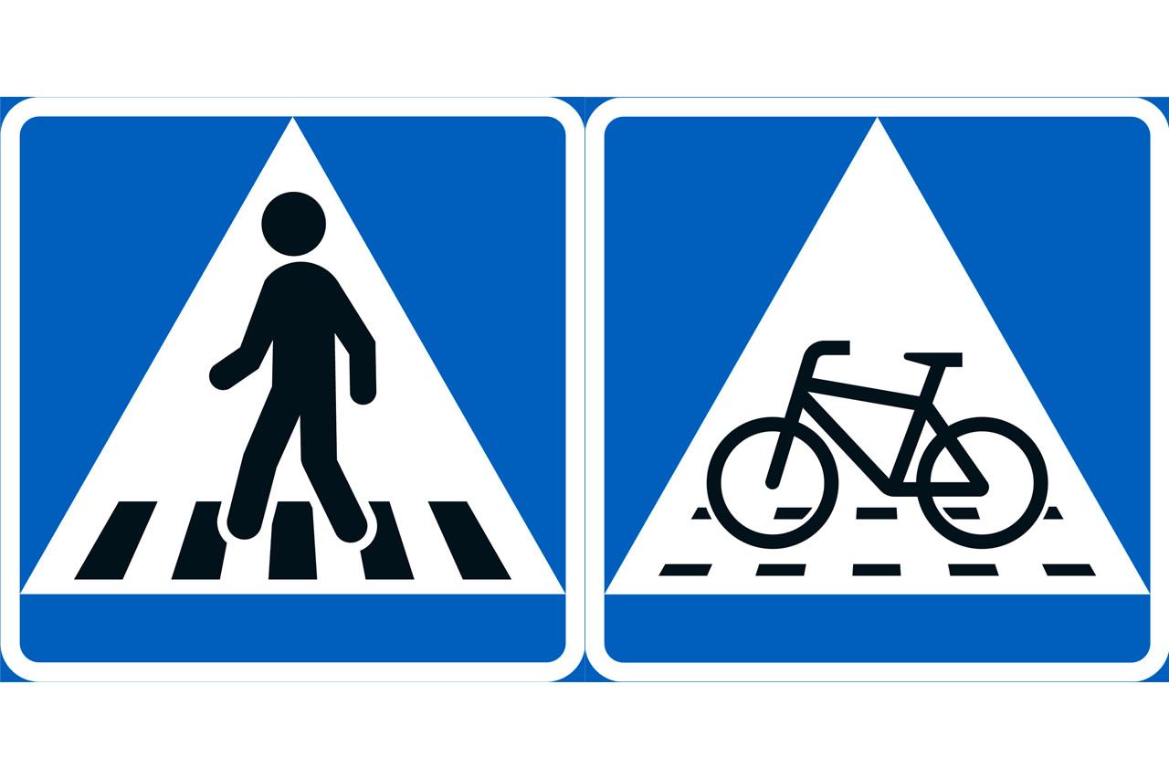 Suojatie-merkki, jossa hahmo kävelee suojatiellä, sekä pyöräilijän tienylitysmerkki, jossa on pyörän kuva ajoradalla.