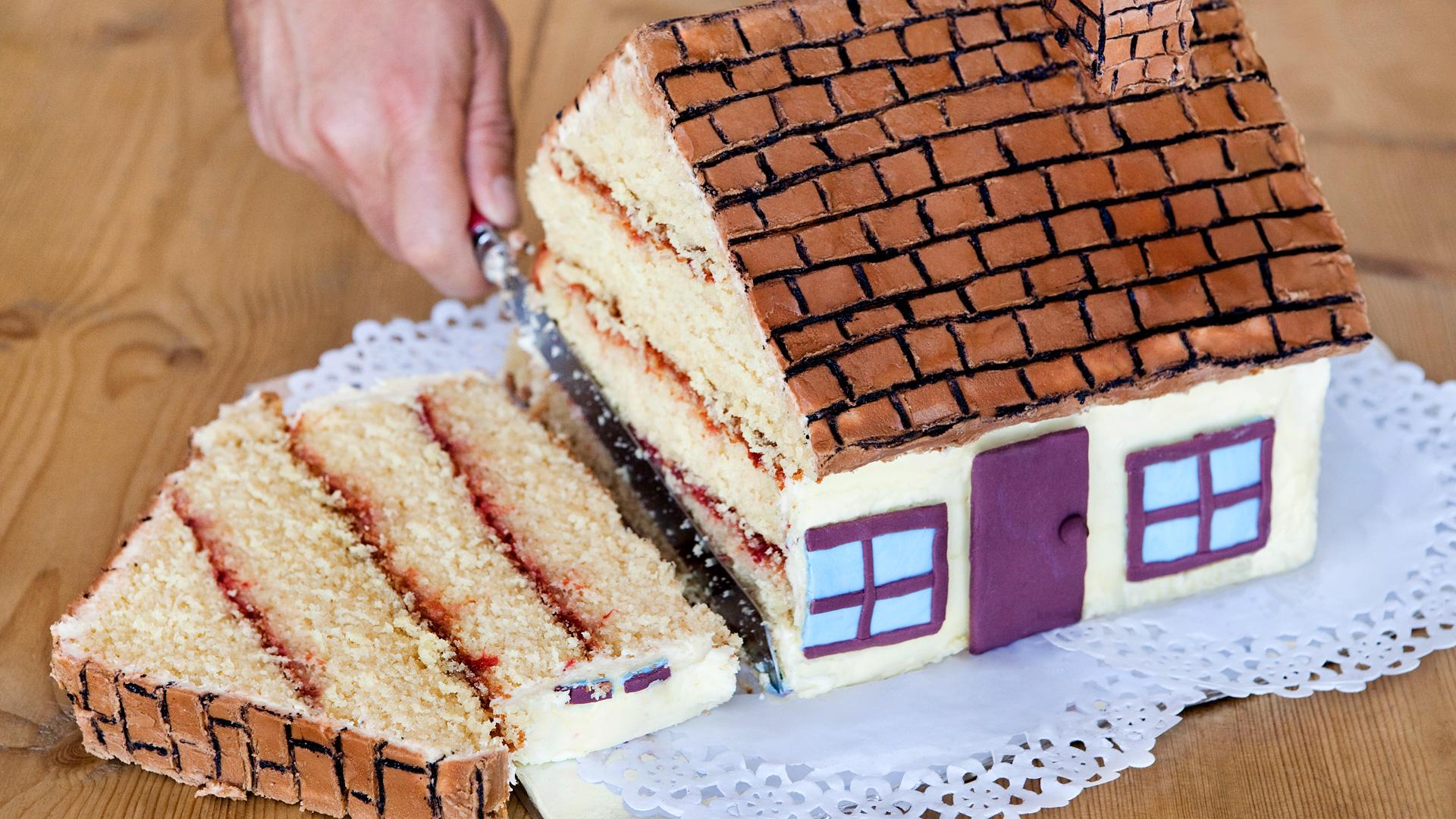 Kakun muotoista taloa leikataan
