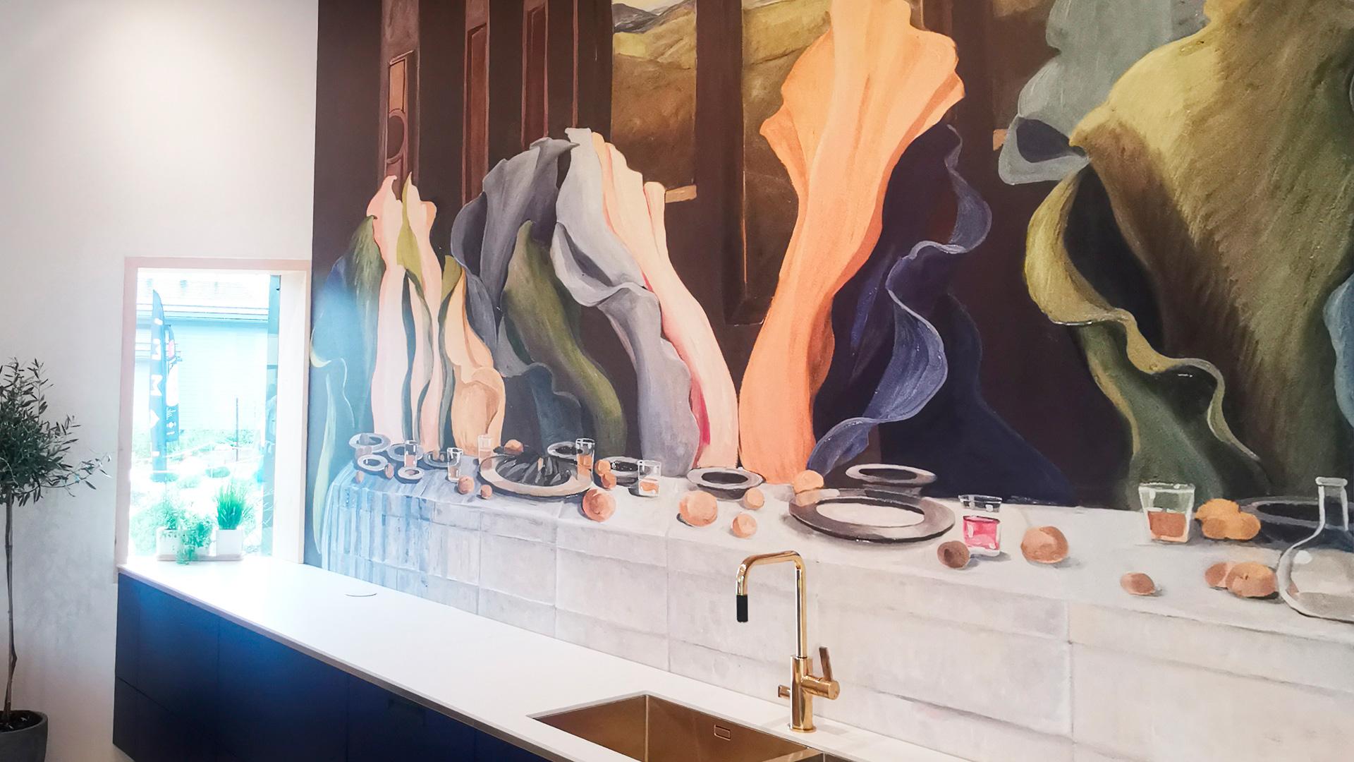"""Pyörre-talon keittiön seinässä on Johanna Oraksen taidetapetti """"Viimeinen ehtoollinen""""."""