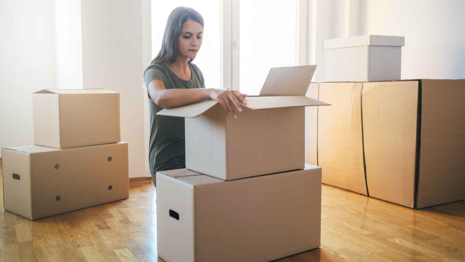 Nainen pakkaa muuttolaatikoita