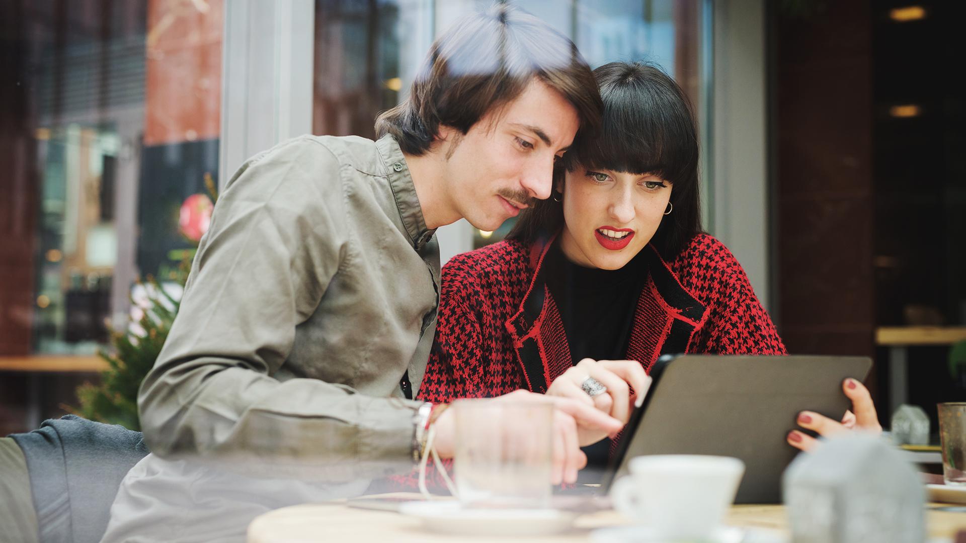 Mies ja nainen kannettavan tietokoneen ääressä