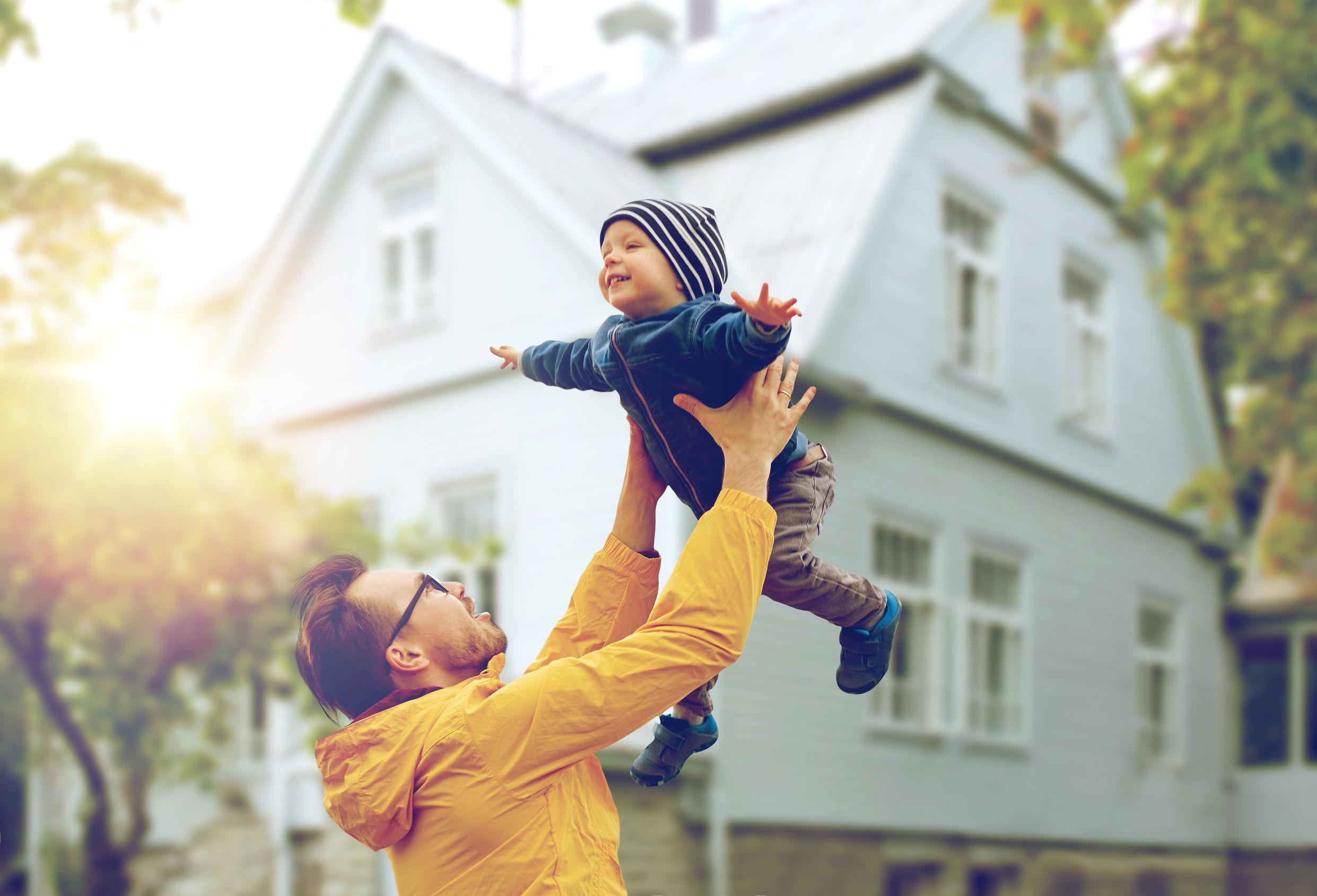 Mies heittää lapsen ilmaan ja lapsi nauraa