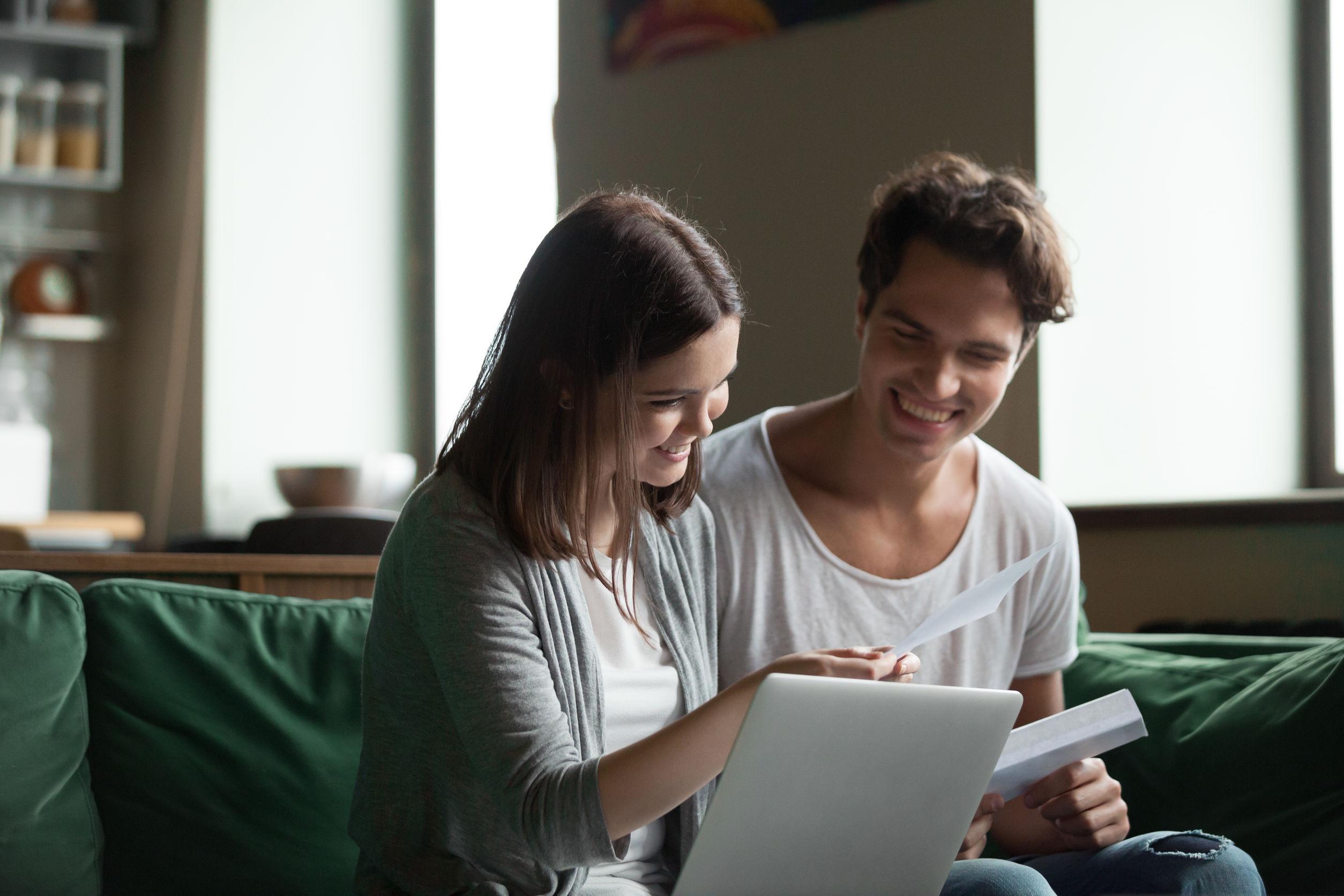 Nainen ja mies katsovat palkkakuittia tietokoneen ääressä